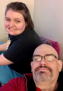 Picture of man with glasses next to a young woman.