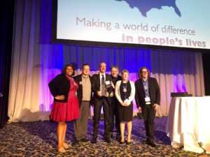 Image of six individuals at Annual Conference. One person is holding an awards.