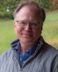 Image of white male with glasses wearing a grey sweater and blue button up shirt.